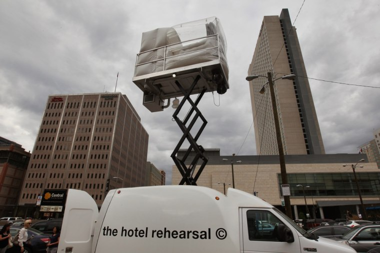 A hotel room made of aluminum and inflated vinyl is held aloft by a van-mounted scissor lift, on promotional display in a parking lot in downtown Denv...