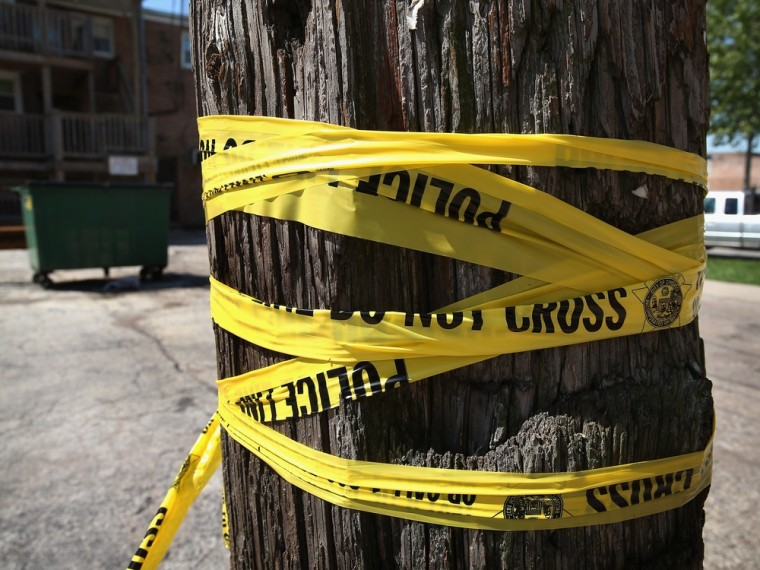 Crime scene tape is wrapped around a power pole near the location where a 20-year-old man died from a gunshot wound to the head and a 15-year-old boy was shot and wounded during weekend violence on May 13, 2013 in Chicago
