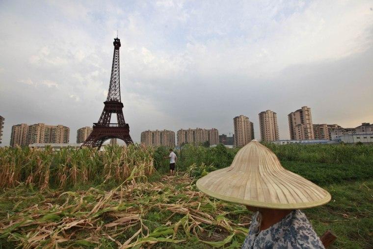 A farmer walks through a field near a replica of the Eiffel Tower at the Tianducheng development in Hangzhou, Zhejiang Province on Aug. 1.