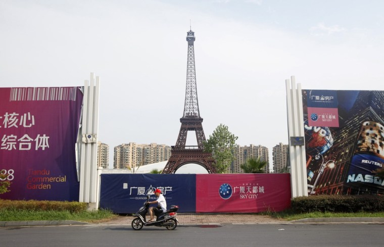 A man rides his motorcycle past a replica of the Eiffel Tower at the Tianducheng development in Hangzhou.