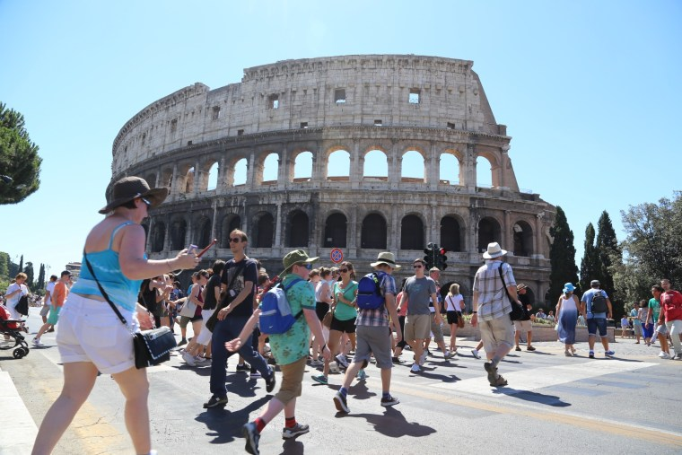 Pedestrians swarm around the Coliseum in Rome Saturday after cars were banned from part of the Via dei Fori Imperiali.