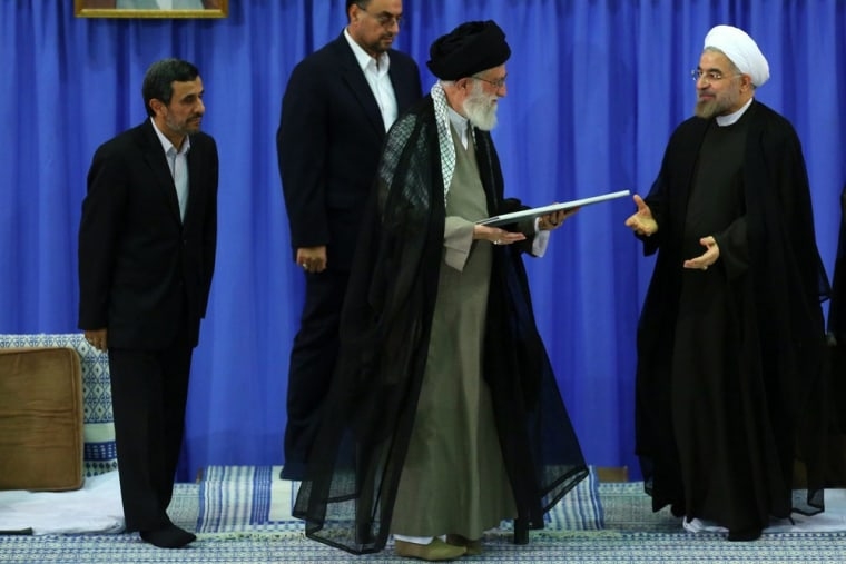 epa03812036 A handout photo made available by Iran's supreme leader website shows Iran's Supreme Leader Ayatollah Ali Khamenei gives the endorsement letter to the new President Hassan Rowhani as ex-president Mahmoud Ahmadinejad looks on.