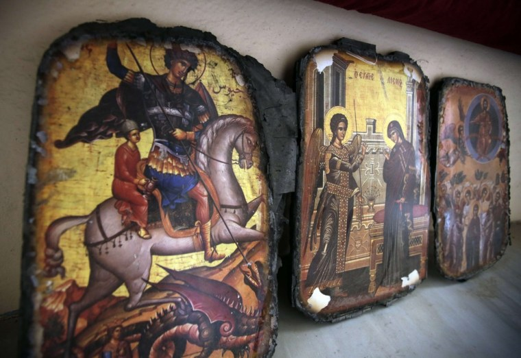 A picture taken on August 1, 2013 shows desecrated icons partially burnt at Saint Elie Church in the city of Qusayr, in Syria's central Homs province.