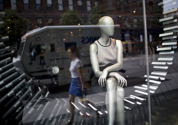 A shopper walks past a store window display in New York, U.S., on Wednesday, July 24, 2013. The U.S. Conference Board is scheduled to release consumer...