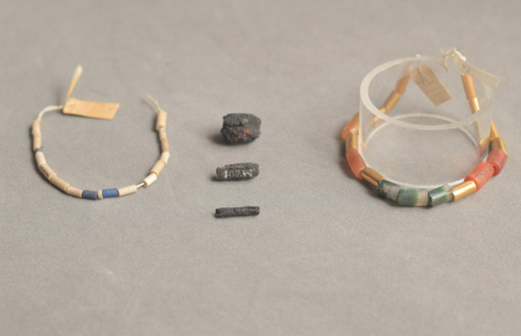 Meteoric iron beads (center) are pictured between ancient Egyptian necklaces that are strung with tube-shaped lapis lazuli (blue), carnelian (brownish/red), agate, and gold beads.