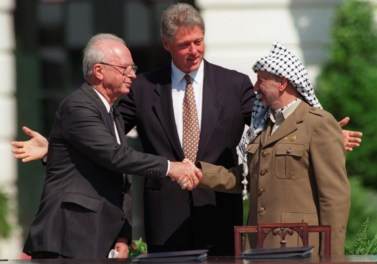 Then Israeli Prime Minister Yitzhak Rabin, left, and PLO Chairman Yasser Arafat, right, shake hands watched by President Bill Clinton on the White House lawn on Sept. 13, 1993. The historic meeting came after the Oslo accord was agreed in secret on Aug. 20.