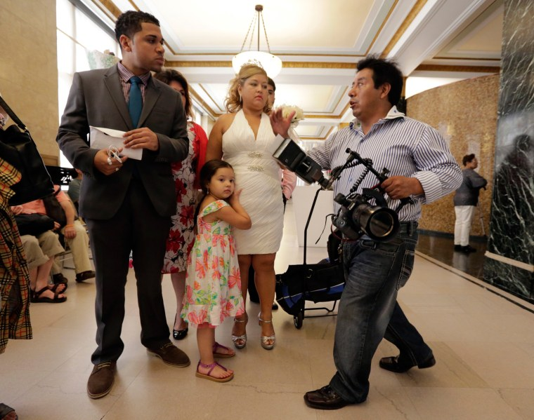 Wedding photographer Braulio Cuenca, right, talks with groom Jorge Mejia and bride Irma Aguilar, from the Bronx, before their ceremony at New York's Office of the City Clerk on Aug. 7, 2013.