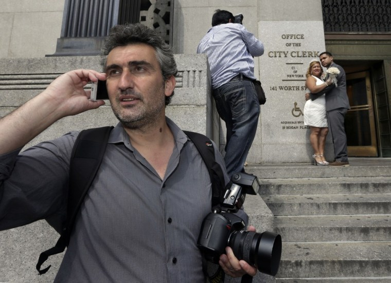 Goran Veljic, left, waits to be hired as Braulio Cuenca shoots pictures of Jorge Mejia and Irma Aguilar outside City Hall. Between them, the two wedding photographers have served as witnesses for thousands of couples.