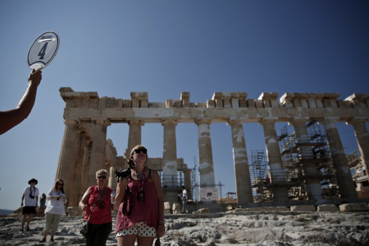 A guide gestures to her group during a visit at the hill of the Acropolis in Athens July 3, 2013. Greek tourism revenues are expected to bounce back t...
