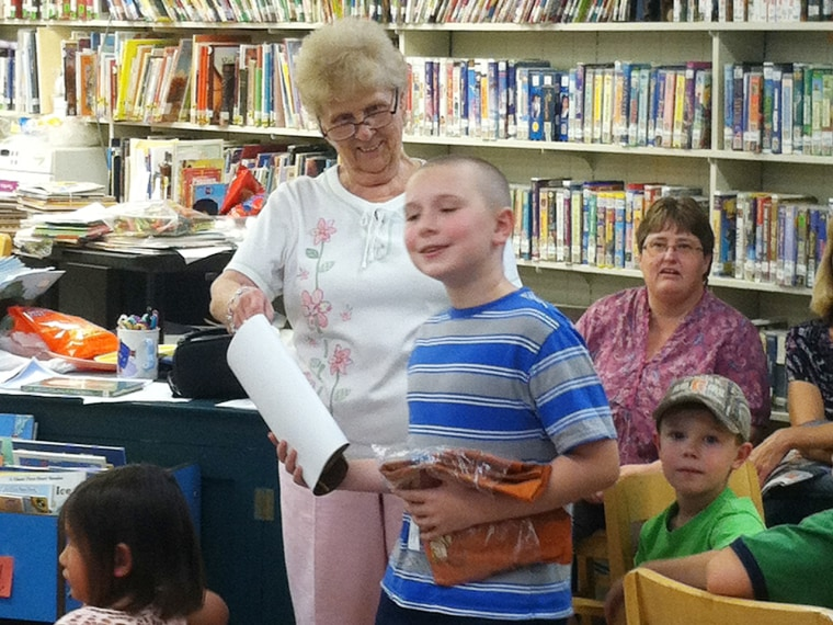 """The mother of Tyler Weaver, 9, has asked for an apology after a local library director in Hudson Falls, N.Y., said she wants Weaver banned from the summer reading contest because he has won it five years in a row and """"hogs'' it for himself. Weaver, above, is shown receiving this year's award from library aide Lita Casey."""