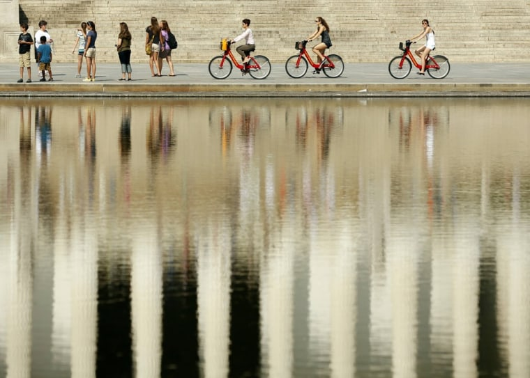 Cyclists ride past the reflecting pool in front of the Lincoln Memorial in Washington, D.C., on Tuesday. The Rev. Dr. Martin Luther King, Jr., deliver...