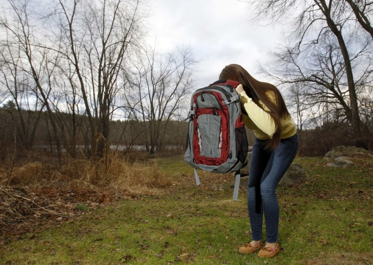 Amanda Curran, 18, daughter of Bullet Blocker inventor Joe Curran, demonstrates how to use a child's bulletproof backpack in the event of a shooting, outside Curran's home in Billerica, Massachusetts December 19, 2012. The child's bulletproof backpacks range in cost from $250 to $600, depending on the size of the backpack.