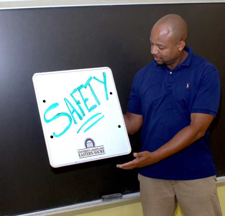 UMES' Marcellus Connor demonstrates how a new type of hand-held writing tablet, similar to stationary whiteboards used in classrooms, can double as bulletproof protection for educators.