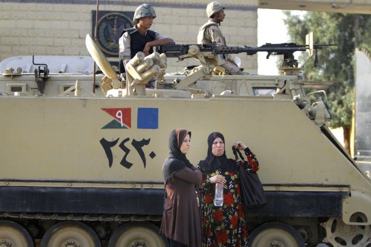 Egyptian women wait near an armored army vehicle guarding Torah Prison, where ousted President Hosni Mubarak is held in Cairo, Egypt, Wednesday, Aug. ...