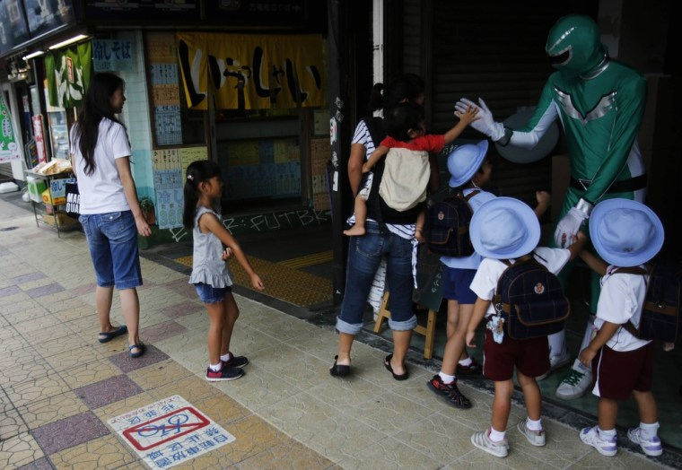 Kanemasu high-fives children at the station where he offers his services.