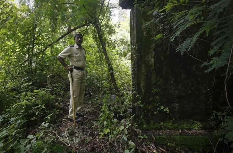 A police officer stands guard on Friday near the location where a photojournalist was raped inside an abandoned textile mill in Mumbai.
