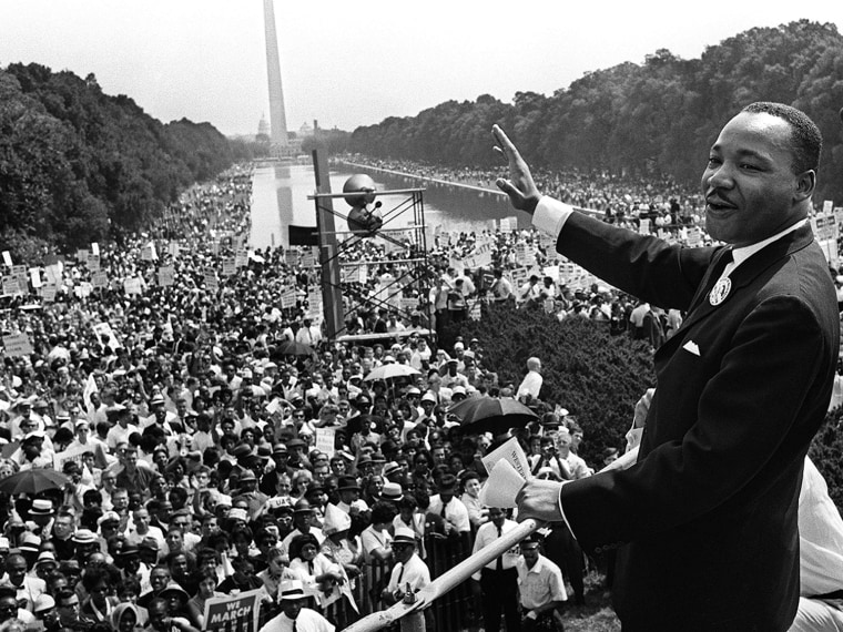Martin Luther King Jr. waves from the steps of the Lincoln Memorial to supporters on the Mall in Washington during the