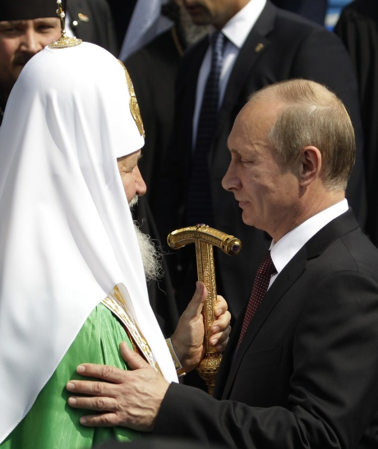 Russian President Vladimir Putin speaks with Russian Orthodox Church Patriarch Kirill, left, during a religious service in Kiev, Ukraine on July 27, 2013.