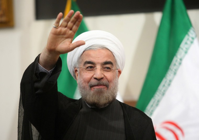 Iranian President-elect Hassan Rouhani waves to reporters during a news conference in Tehran on June 17.