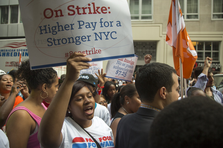 Zenquetta Charles (with sign) of Brooklyn, protests outside the Burger King in New York City's financial district where she works as a cashier for $7....