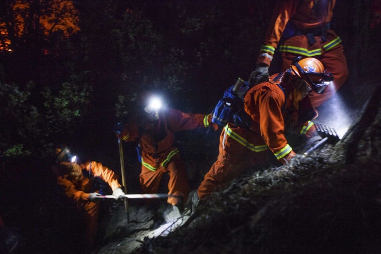 The McCain inmate crew out of San Diego struggles to cut a fire line on a steep slope on the Rim Fire near Buck Meadows, Calif.