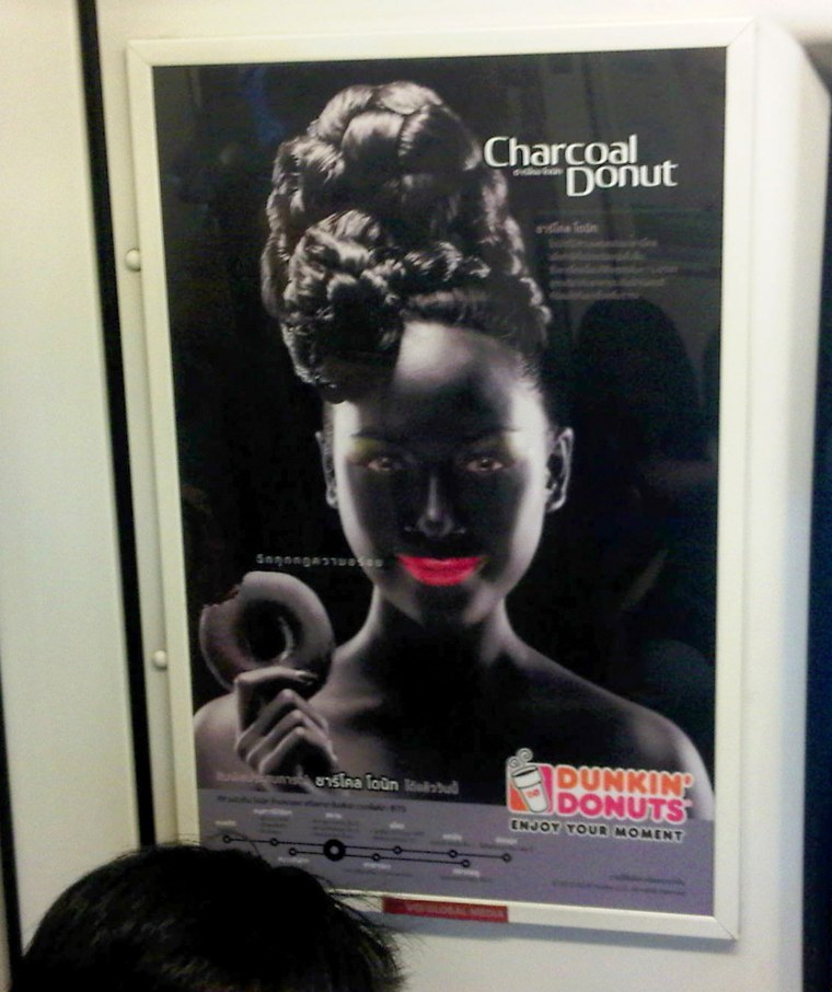 An advertisement poster of a smiling woman with bright pink lips in blackface makeup holding a doughnut is seen on a Skytrain, a commuter train in Ban...