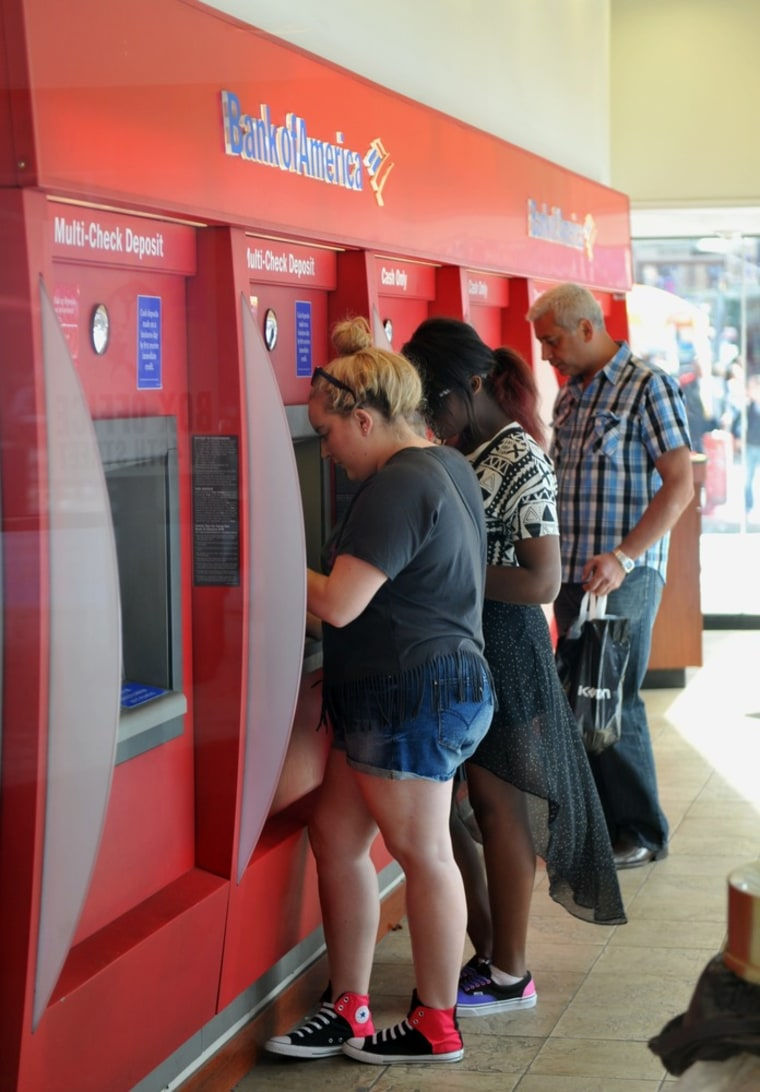 (FILES)People use automatic teller machines at a Bank of America branch in this June 26, 2012 photo in New York's Times Square.   Bank of America repo...