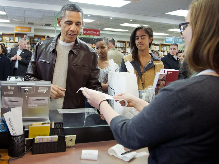 President Barack Obama, with daughters Sasha, center, and Malia, pays for his purchase the the local bookstore Politics and Prose in northwest Washing...