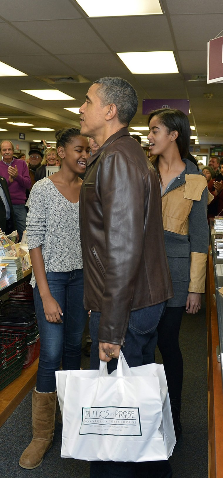 epa03971703 US President Barack Obama holds a bag of his book purchases after he and daughters Malia (R) and Sasha did some shopping at the independen...