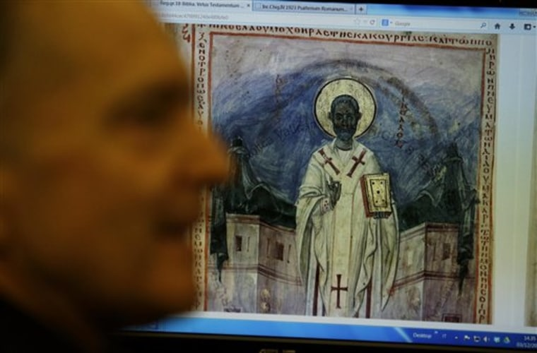 Msgr. Cesare Pasini, prefect of the Vatican Apostolic Library, shows a 10th century digitalized Bible during an interview with The Associated Press , ...