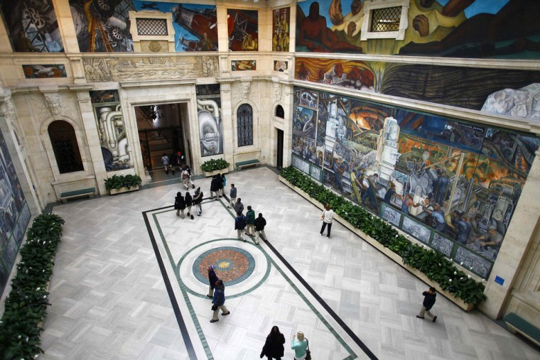 People look at a mural by artist Diego Rivera at the Art Institute of Detroit in Detroit, Michigan December 3, 2013.