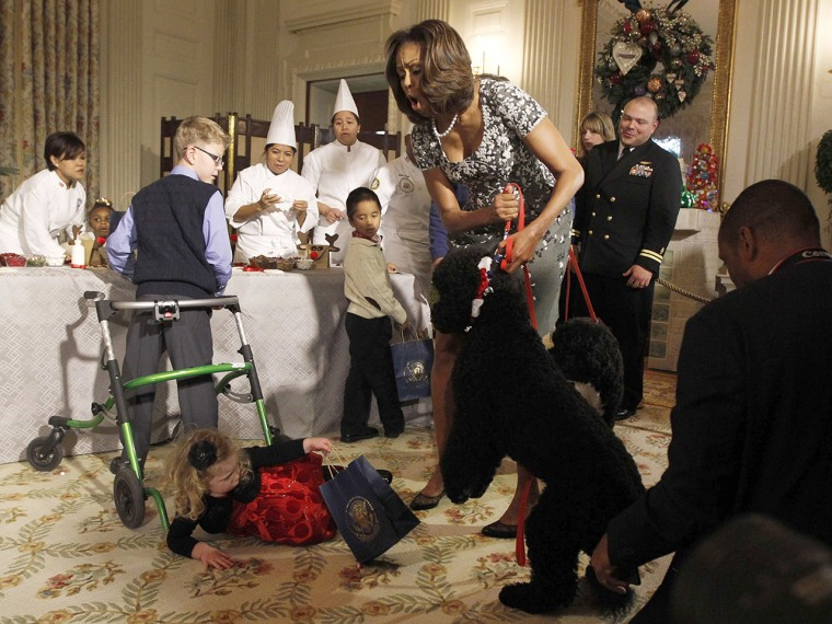 U.S. first lady Michelle Obama reacts as two year old Ashtyn Gardner from Mobile, Alabama, trips over another child's walker after meeting Obama's new...