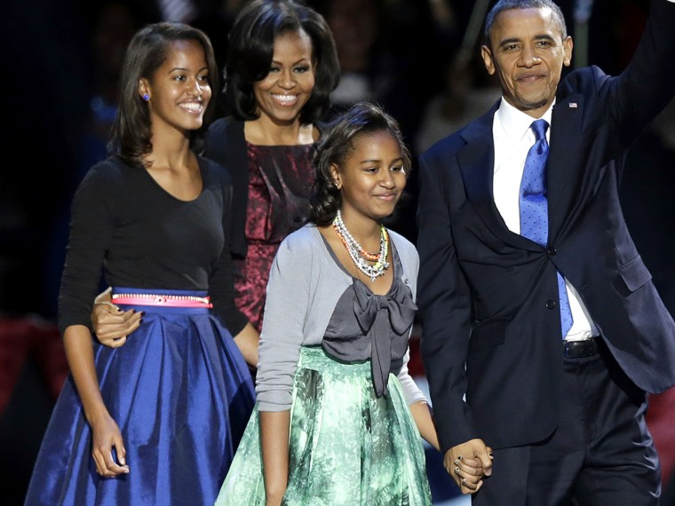 President Barack Obama waves as he walks on stage with first lady Michelle Obama and daughters Malia and Sasha at his election night party Wednesday, ...