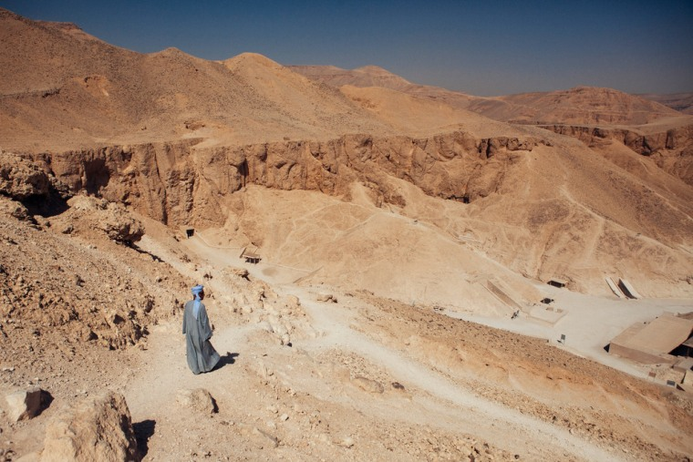 LUXOR, EGYPT - OCTOBER 23: An Egyptian man, a custodian of the Valley of the Kings, stands on a hill overlooking the Valley of the Kings on October 2...