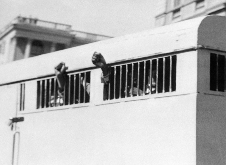 Eight men, among them anti-apartheid leader and African National Congress (ANC) member Nelson Mandela, sentenced to life imprisonment in the Rivonia trial leave the Palace of Justice in Pretoria 16 June 1964 with their fists raised in defiance through the barred windows of the prison car.