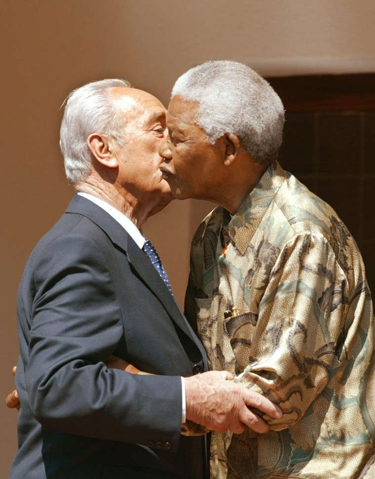 Former South African President Nelson Mandela (R) kisses Israeli Foreign Minister Shimon Peres in 2002 after a meeting at Mandela's office in Johannesburg.