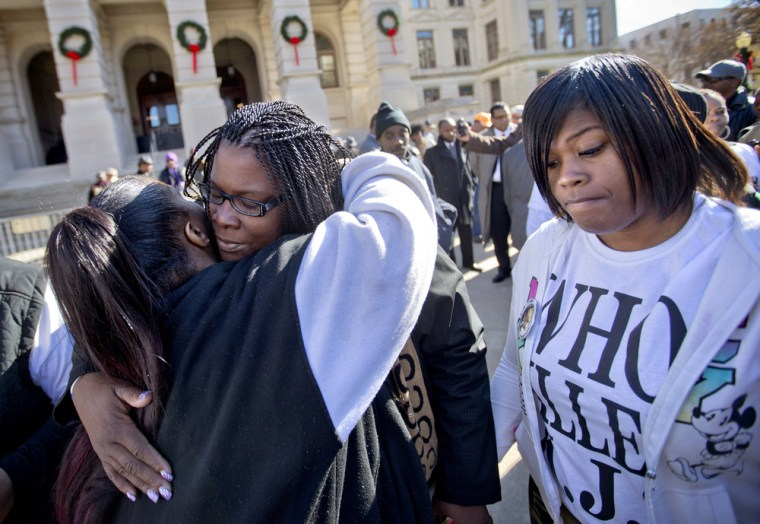 Jacquelyn Johnson, second from left, the mother of Kendrick Johnson, the south Georgia teenager found dead inside a rolled-up wrestling mat in his school, is embraced by Monique Mosely, left, as Johnson's daughter Kenyetta, right, stands by following a rally, Wednesday, Dec. 11, 2013, in Atlanta.