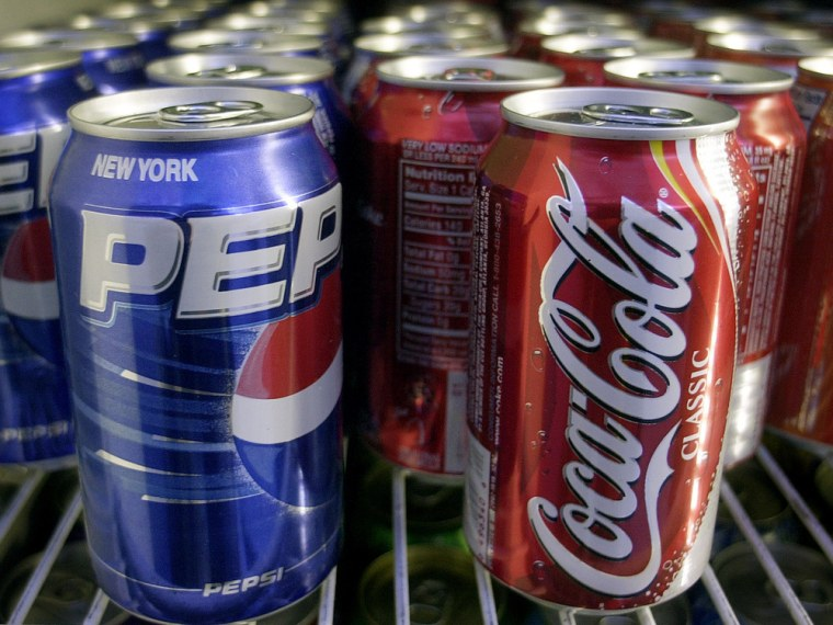 ** FILE ** Cans of Pepsi and Coke are shown in a news stand refrigerator display rack in a New York file photo from April 22, 2005. It wasn't locked u...