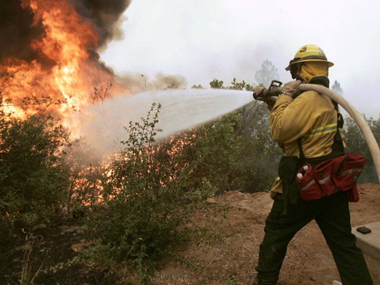A firefighter hoses down flames from the Butte Lightening Complex fire as they approach a fire line near Concow, Calif., Thursday, July 10, 2008. Th...