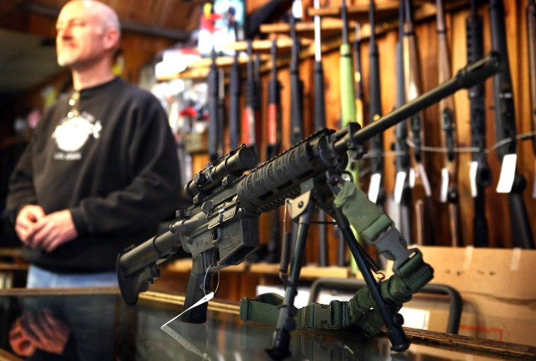 An AR-15 style rifle sits on the counter by Craig Marshall as he assists a customer at Freddie Bear Sports sporting goods store on December 17, 2012, in Tinley Park, Ill.
