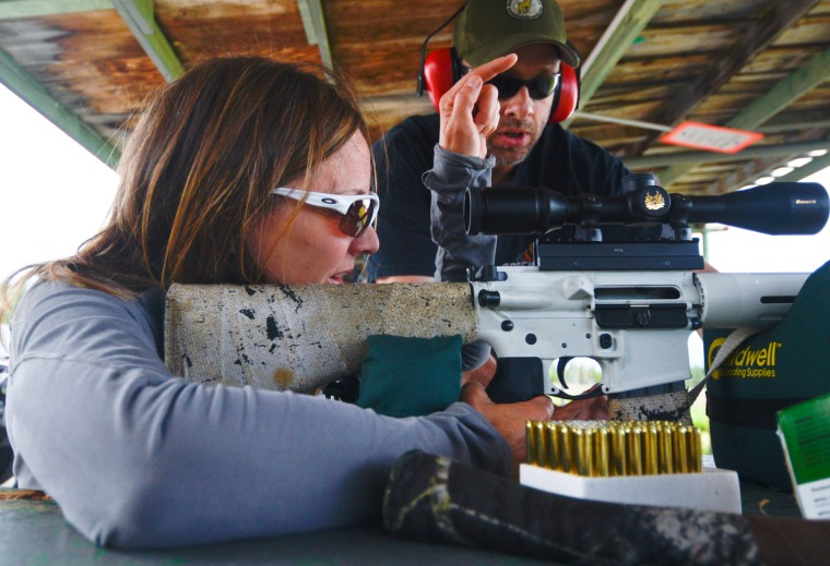 In this Saturday Aug. 3, 2013, photo Kym Cross gestures down the shooting range as Loren Reese helps her aim an AR-15 during a Women on Target class at the Snowshoe Gun Club in Kenai, Alaska.