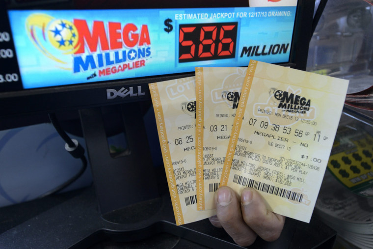 A salesman holds Mega Millions lottery tickets at a retailer in Decatur, Georgia, USA, 16 December 2013.