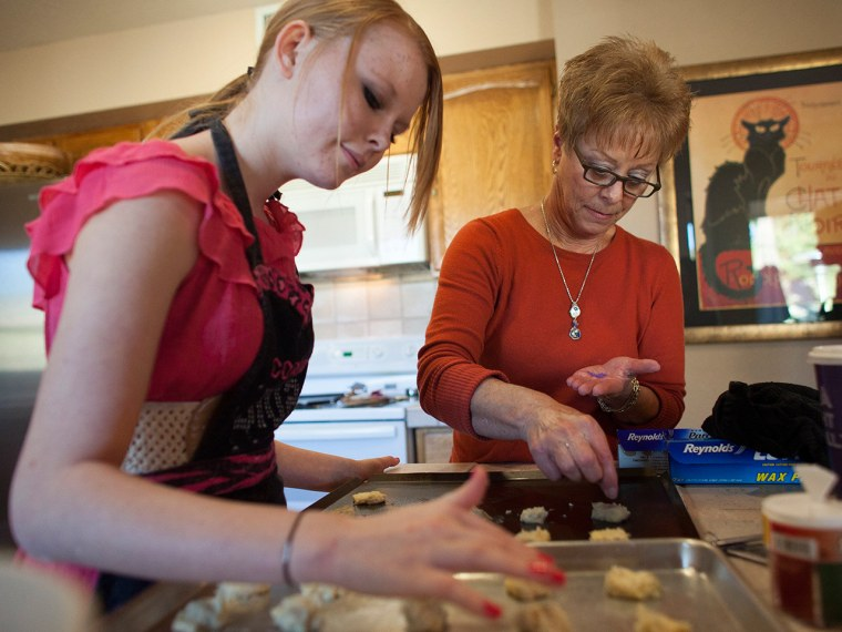 Davis helps her granddaugher, Hunter Hill, 15, bake holiday cookies at her home in Mesa, Ariz.