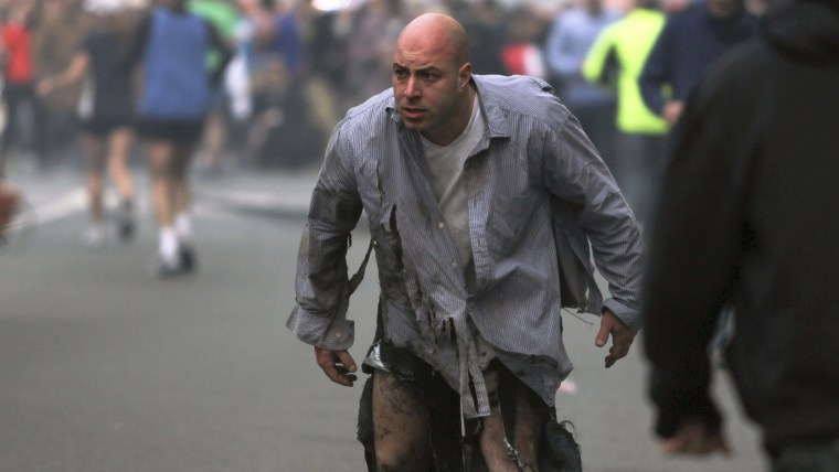 In this photo provided by The Daily Free Press and photographer Kenshin Okubo, Boston Marathon bombing victim James Costello staggers away in his torn...