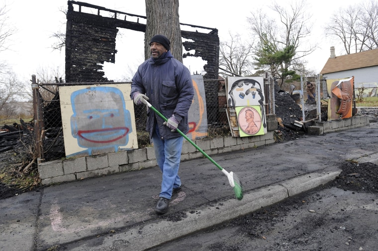 Tyree Guyton sweeps up debris at the Penny House at the Heidelberg Project in Detroit on Thursday, Nov. 21, 2013, after a fire destroyed the building.