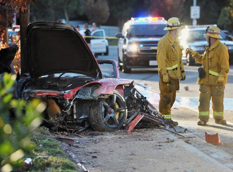 First responders gather evidence near the wreckage of a Porsche sports car that crashed into a light pole on Hercules Street near Kelly Johnson Parkwa...