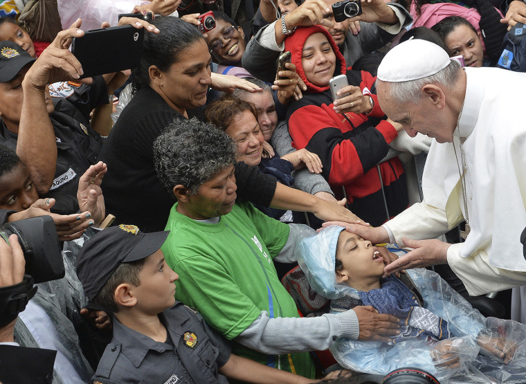 Pope Francis blesses a child during his visit to the Varginha slum in Rio de Janeiro, Brazil, on July 25, 2013. Francis visited one of Rio de Janeiro's shantytowns, or favelas, a place that saw such rough violence in the past that it's known by locals as the Gaza Strip.