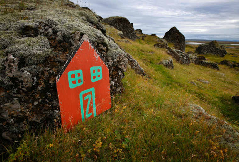 An elf door leans against a rock in the Icelandic countryside outside the village of Selfoss in 2006. Belief in the unseen runs so high in Iceland that the Public Roads Administration sometimes delays or reroutes road construction to avoid what locals believe are elf habitations or cursed spots.