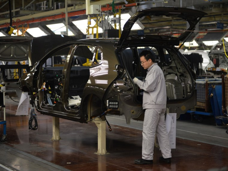 Photo taken on December 7, 2013 shows workers on the assemby line at the Sino-French joint venture Dongfeng Peugeot-Citroën Automobile (DPCA) plant in...