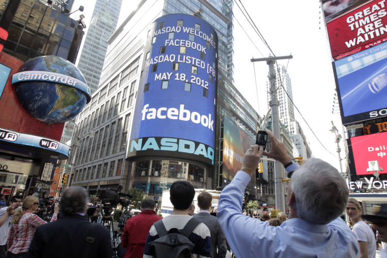 A man stops to photograph Nasdaq in Times Square as Facebook has its IPO, Friday, May 18, 2012, in New York. The social media company priced its IPO o...